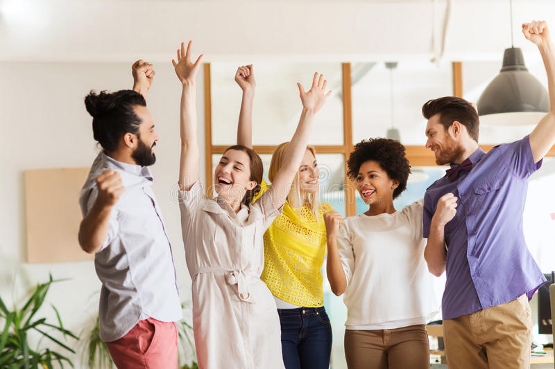 Happy creative team celebrating victory in office royalty free stock photos