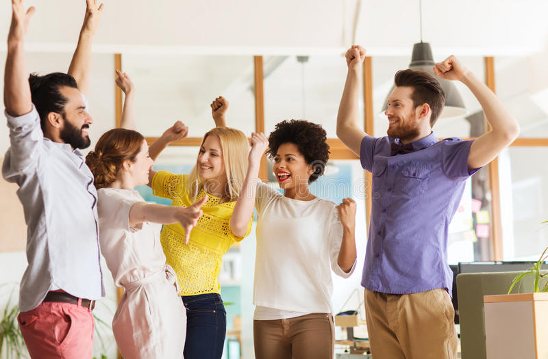 Happy creative team celebrating victory in office stock images