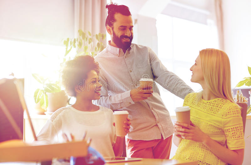 Happy creative team drinking coffee in office royalty free stock photography