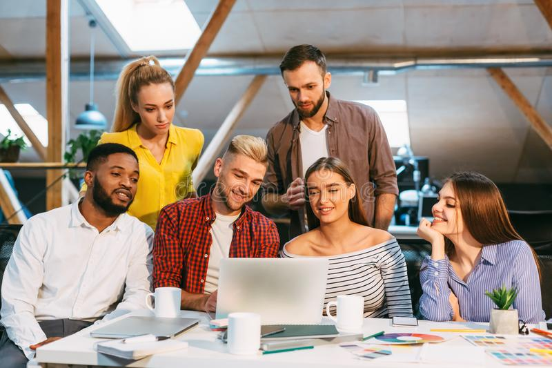 Happy creative team using laptop at meeting in office stock photography
