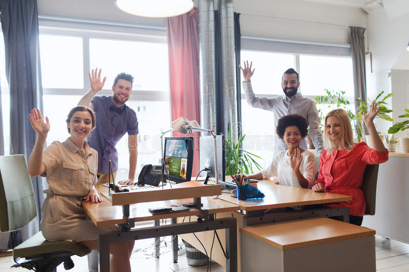 Happy creative team waving hands in office royalty free stock photo