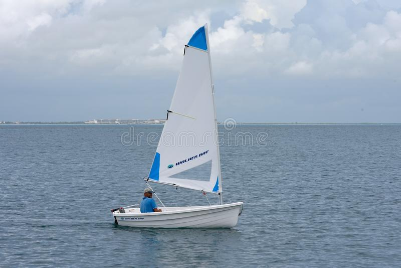 Sailing dinghy. Happy cruiser going ashore from his boat in anchorage with sailing tender, rigid plastic dinghy Walker Bay. Mexico. Isla Mujeres stock photo