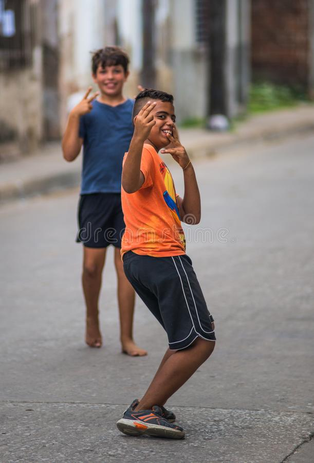 Happy Cuban child portrait in poor Caribbean colonial street alley with smile and friendly face, in old city, Cuba, America. stock photo