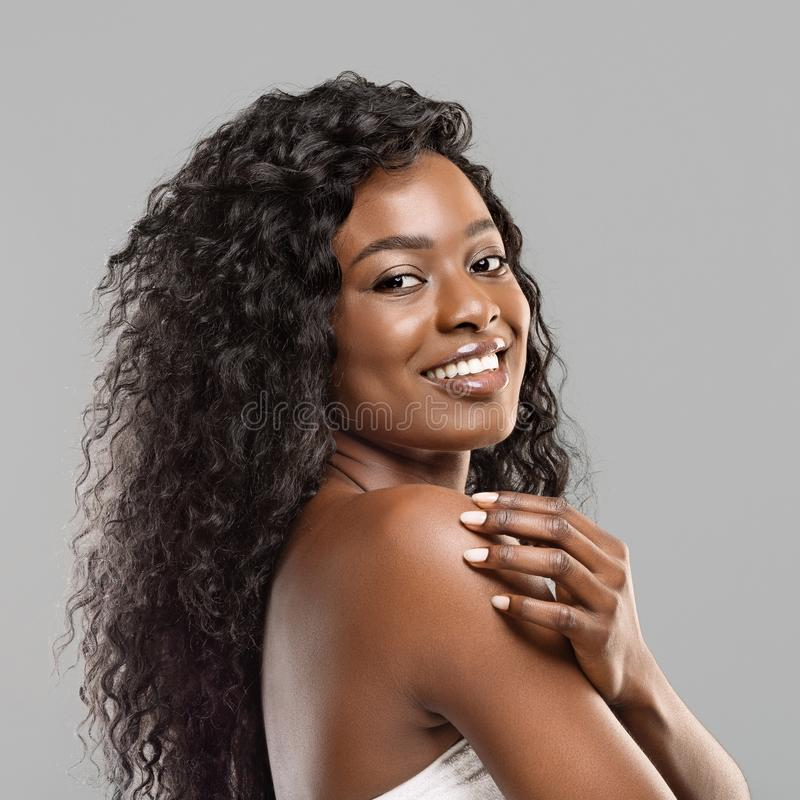 Happy curly black girl with clean fresh skin and perfect smile. Natural beauty. Portrait of happy black girl with clean fresh skin and perfect smile over grey stock image