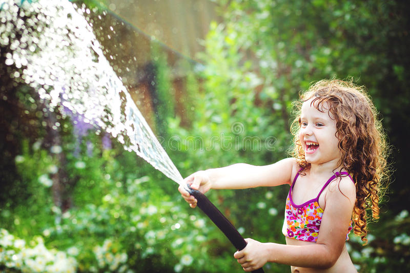 Happy curly girl under water splashes in the summer garden. stock image