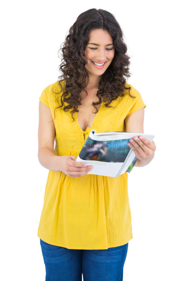 Happy curly haired brunette reading magazine. Happy curly haired brunette on white background reading magazine stock photos