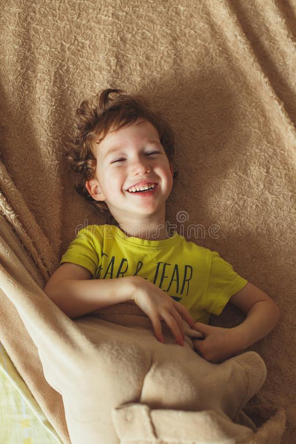 Happy curly toddler baby having fun in bed. Cute boy smiling. Vertical photo royalty free stock images