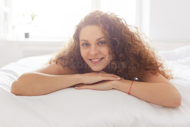 Happy curly young woman with pleasant appearance, lies on comfortable bed, enjoys good rest in bedroom and Saturday morning stock photos
