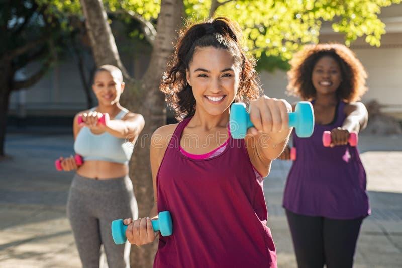 Happy curvy women using dumbbells stock image