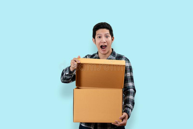 Happy customer asian man excited expression opening and holding. Box looking at camera with isolated background feeling surprise and satisfaction. Unbox concept stock photos