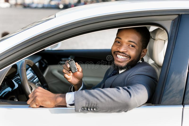 Happy customer just bought new auto at car dealership. Sitting on driver`s seat and smiling to camera royalty free stock photo