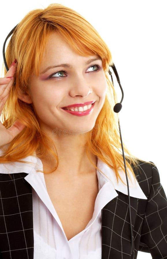 Happy customer service girl. Smiling customer service redhead lady using headset stock photo