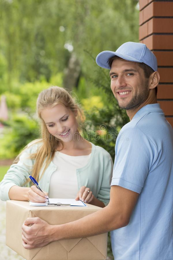 Customer signing receipt of box delivery by smiling courier with blue cap. Happy customer signing receipt of box delivery by smiling courier with blue cap stock photos