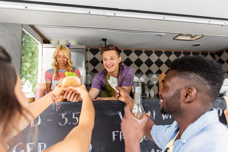 Happy customers buying burger at food truck. Street sale, payment and people concept - happy customers buying burger at food truck stock photo