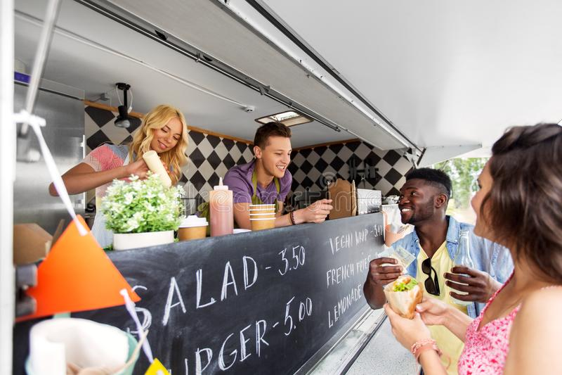 Happy customers buying burger at food truck. Street sale, payment and people concept - happy customers buying burger at food truck royalty free stock images