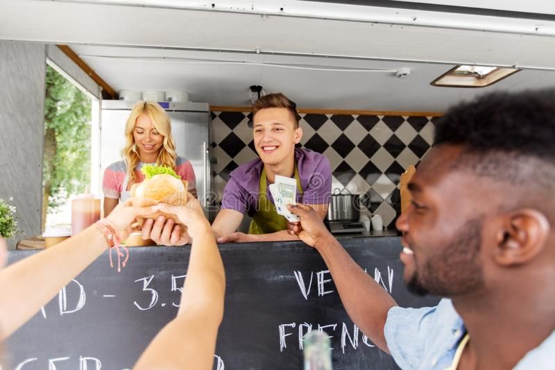 Happy customers buying burger at food truck. Street sale, payment and people concept - happy customers buying burger at food truck stock images