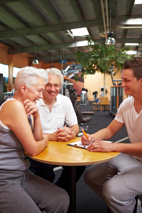 Happy customers in gym. Fitness trainer in gym talking to new customers royalty free stock images