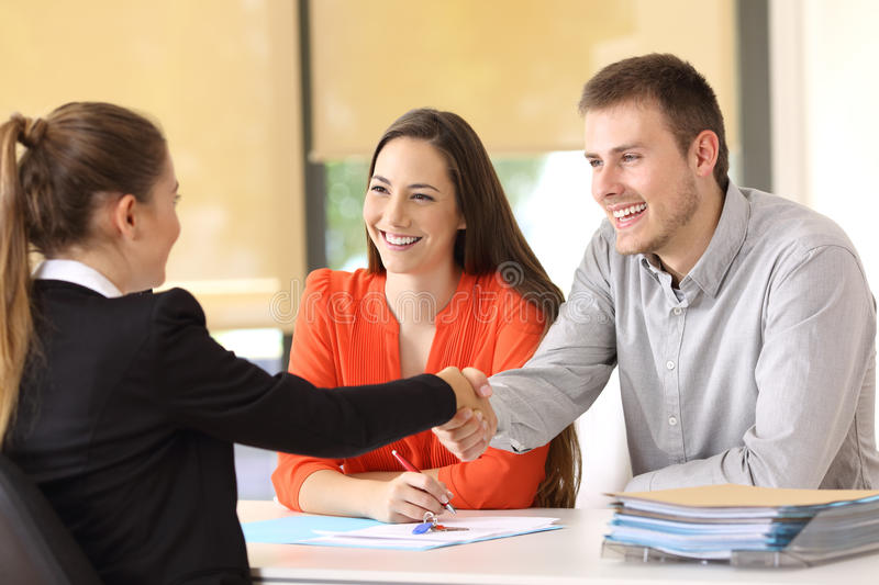 Happy customers handshaking after a deal. Couple of happy customers handshaking with worker after a deal at office royalty free stock images