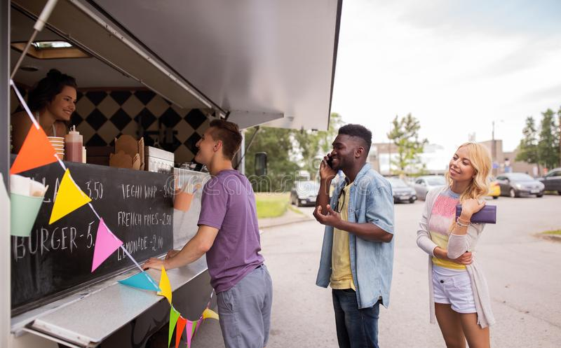 Happy customers queue at food truck stock photography