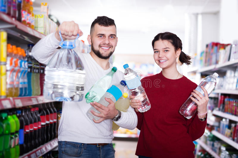 Happy customers standing at beverages section. Portrait of happy customers standing at beverages section of supermarket stock images