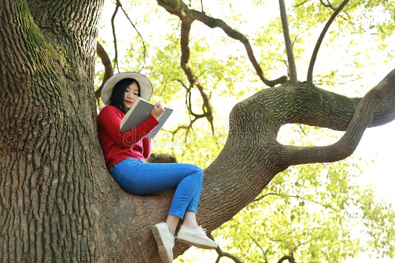 Happy cute Asian Chinese nature beautiful woman girl in a spring park enjoy free time read book royalty free stock image