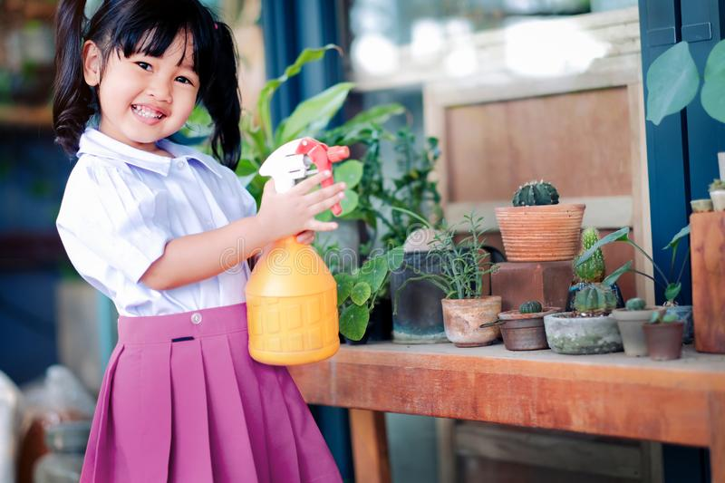 Happy Cute Asian Girl Enjoying with Gardening Activities, A Three Years old Child in Student Uniform is Watering Plant in the stock image
