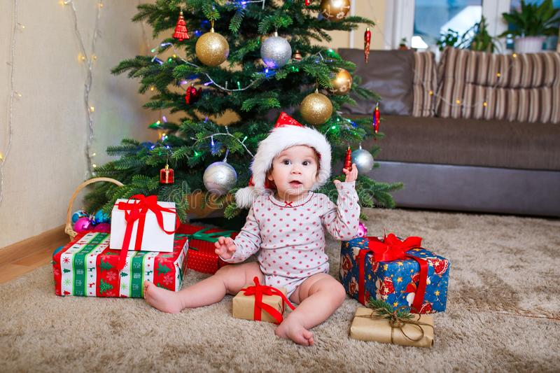 Happy cute baby girl in Santa Claus hat holding Christmas gifts at christmas tree at home stock image