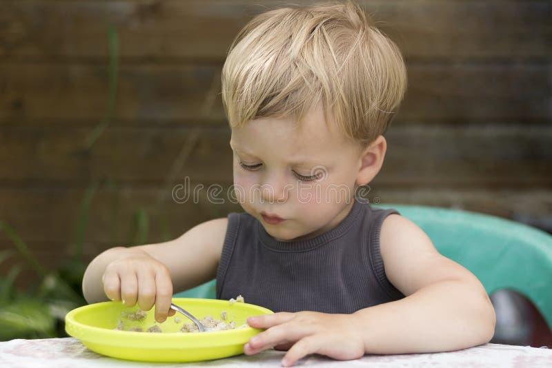 Happy cute baby kid boy eating porridge itself with spoon royalty free stock photos