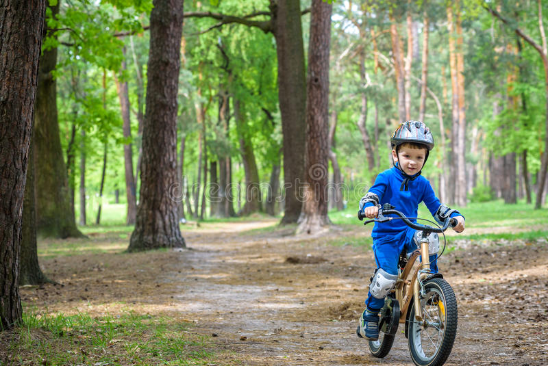 Happy cute blond kid boy having fun his first bike on sunny summer day, outdoors. child making sports. Active leisure for royalty free stock photography