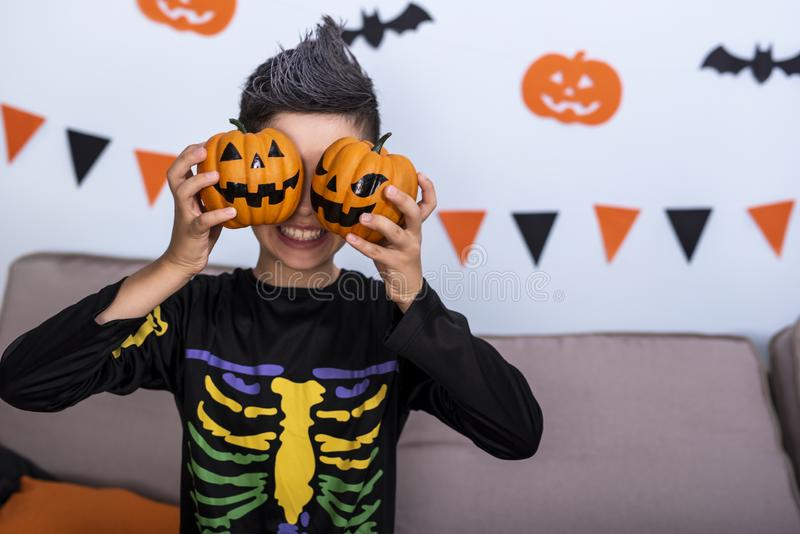Happy cute boy in costume during Halloween party, holding pumpkin Jack-o`-lantern covering his eyes. Happy cute boy girl in costume during Halloween party stock photography