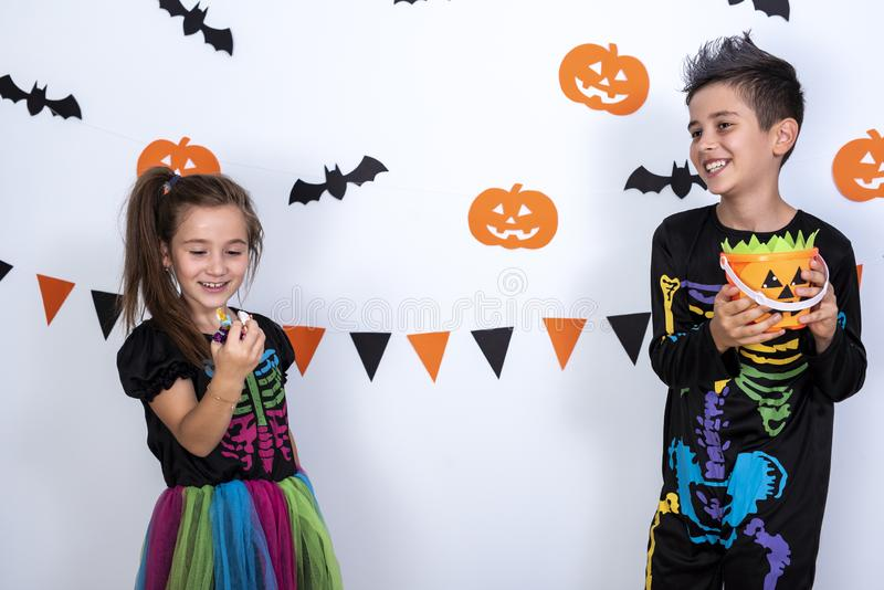 Happy cute boy and girl in costume during Halloween party, holding pumpkin Jack-o`-lantern trying to eat candies from it. Happy cute boy girl in costume during royalty free stock photos