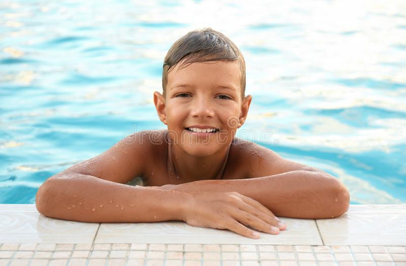 Happy  boy in swimming pool. Happy cute boy in swimming pool royalty free stock photos