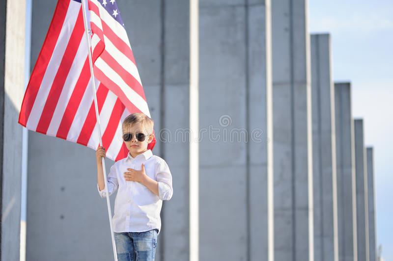 A boy with American flag. Happy cute boy waving American flag outside, wearing white shirt and jeans. Child celebrating 4th july - Independence Day of USA stock photo