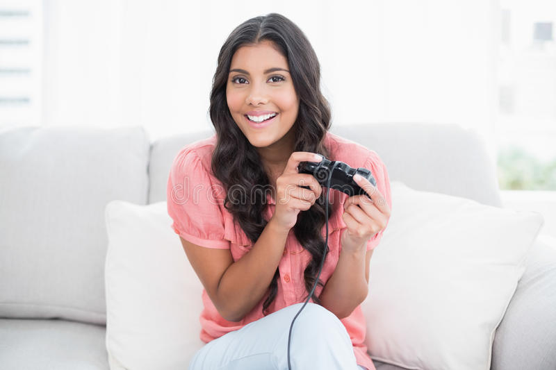 Happy cute brunette sitting on couch holding controller stock image