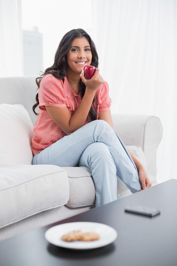 Happy cute brunette sitting on couch holding red apple royalty free stock photo