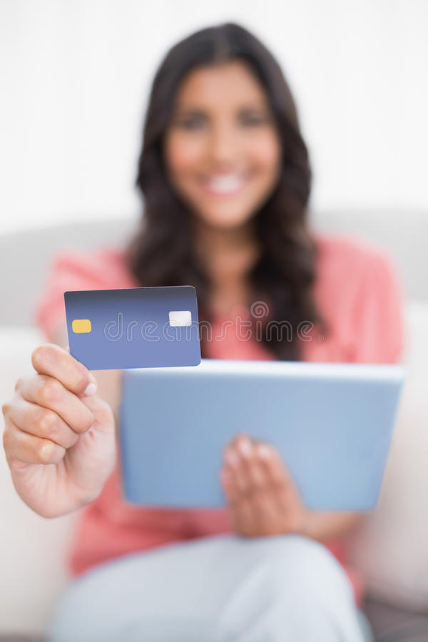 Happy cute brunette sitting on couch showing credit card holding tablet royalty free stock photos