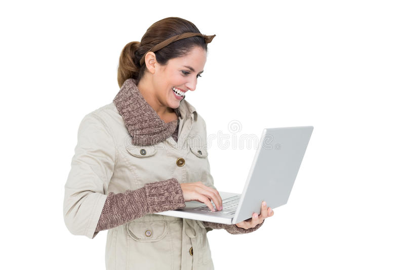 Happy cute brunette in winter fashion using laptop stock image