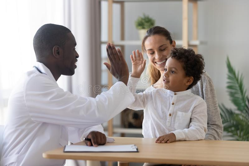 Happy cute child boy give high five to african pediatrician royalty free stock photos
