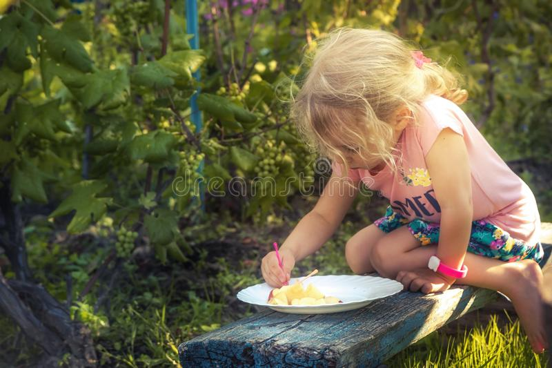 Happy cute child girl eating fresh fruits in summer garden concept healthy eating countryside lifestyle royalty free stock photography