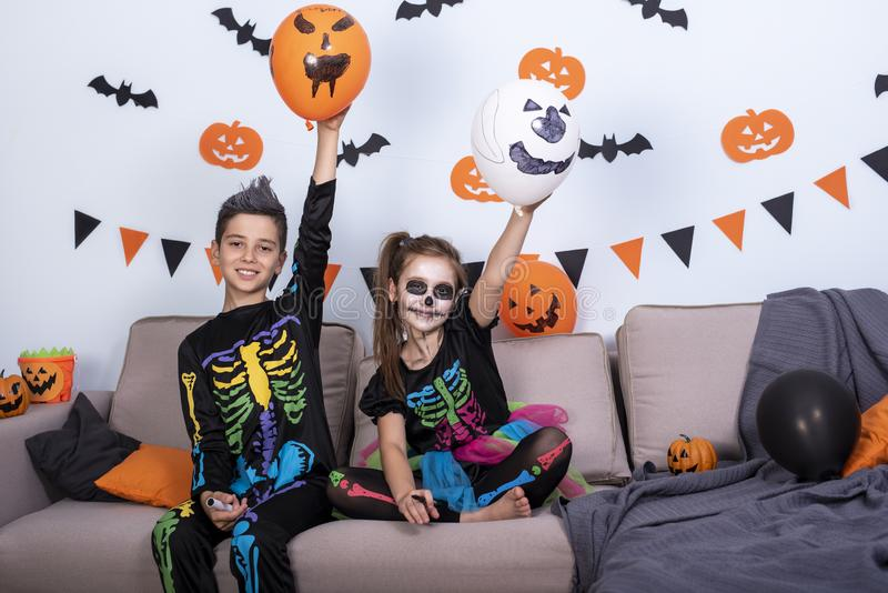 Happy cute children boy and girls in costume on sofa in living room during Halloween party. Happy cute children boy and girls in costume on sofa in living room stock photo