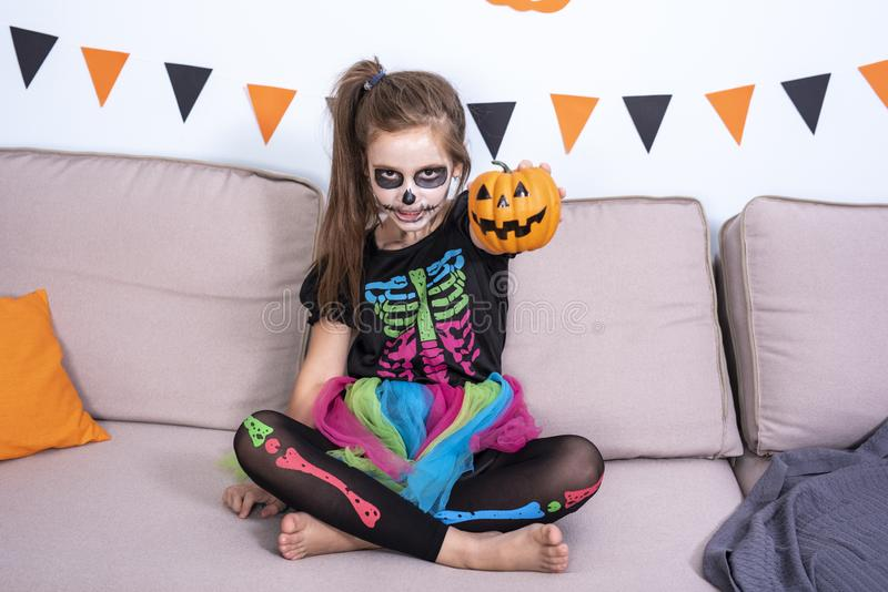 Happy cute children girl in costume on sofa in living room with a pumpkin in the hand during Halloween party. Happy cute children boy and girls in costume on royalty free stock image