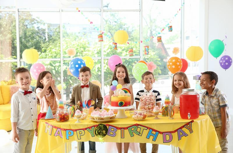 Cute children near table with treats at birthday party indoors stock photo