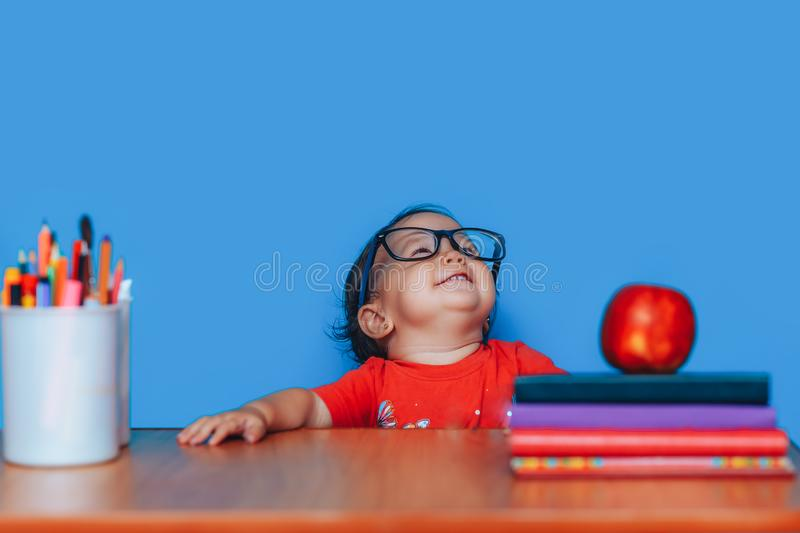 Happy cute clever girl is sitting at a desk in glasses. Preschool girl in glasses. Early education.  royalty free stock photos