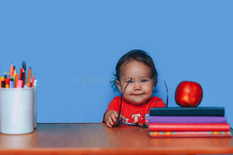 Happy cute clever girl is sitting at a desk in glasses. Preschool girl in glasses. Early education.  stock images