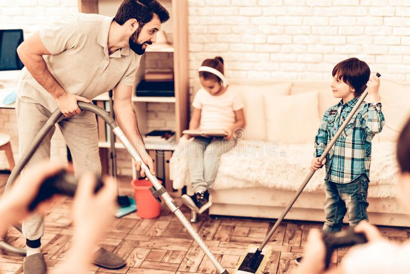 Happy Cute Father Cleaning Room with Kids. Father Cleaning Floor with Son. Game Concept. Mom with Daughter controls the Real Character. Kids Helping House stock image