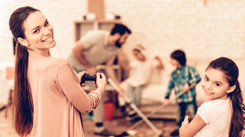 Happy Cute Father Cleaning Room with Kids. Father Cleaning Floor with Son. Game Concept. Mom with Daughter controls the Real Character. Kids Helping House royalty free stock image