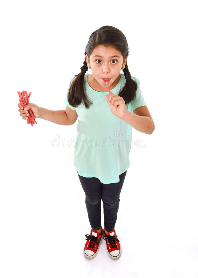 Happy cute female child licking and eating red licorice candy in kid love sweet and sugar concept stock images