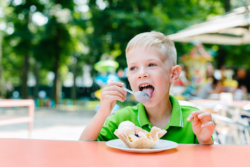 Happy cute funny boy is eating ice cream in cafe stock images