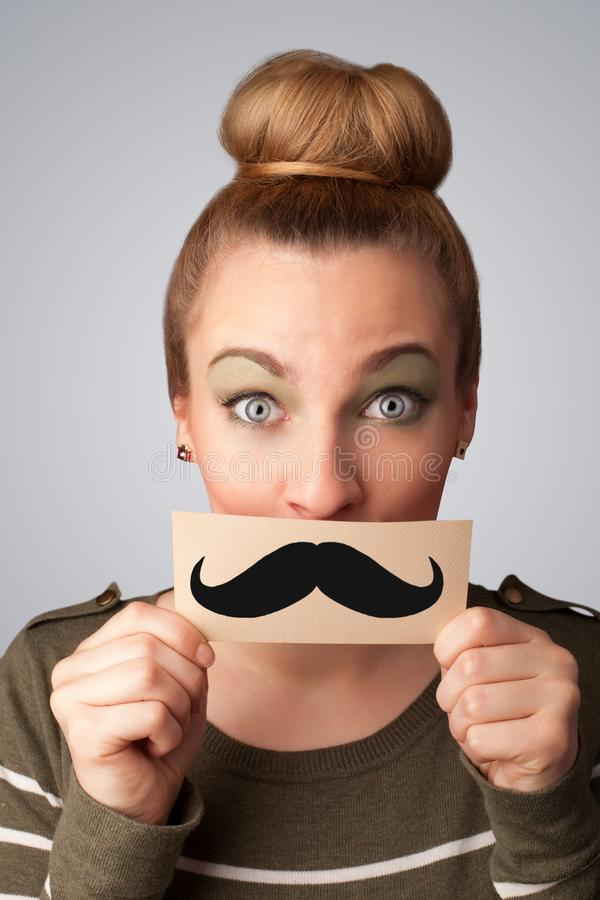Happy cute girl holding paper with mustache drawing. On gradient background royalty free stock images