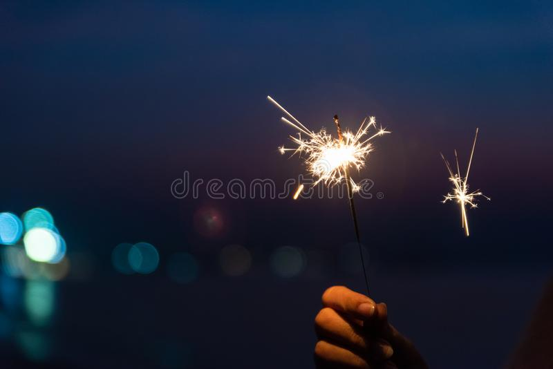 Happy cute girl holding a sparkler on beach during sunset. Celebration concept.  stock photos